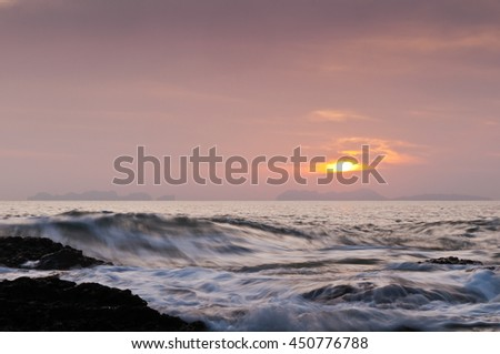 The landscape with sunset over the sea and waves