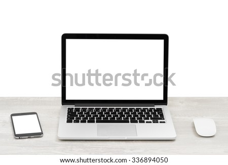 The laptop on the table with the mouse and smartphone - stock photo