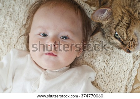 The large house cat lying near newborn baby