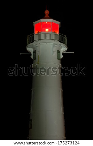 The larger of two range lights, this white lighthouse in Munising, Michigan shines a continuous red light. - stock photo