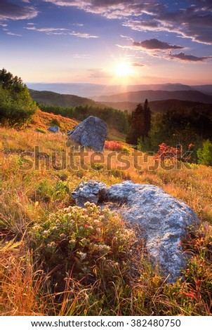 The last, warm light of day fills Routt National Forest.  Steamboat Springs and the Yampa River lie in the distant valley. - stock photo