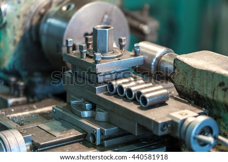 The lathe is in operation, revolves the spindle, the machine studded with steel shavings. A few finished parts in the frame