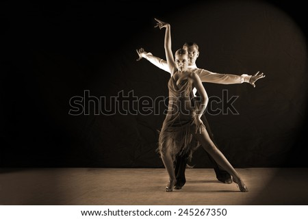 The Latino dancers in ballroom against black background - stock photo