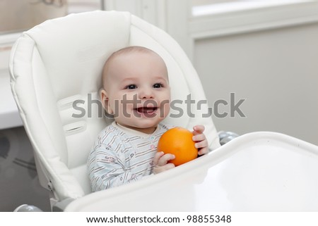 The laughing baby with orange in a highchair