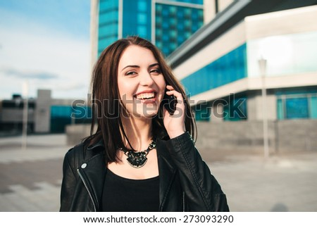 The laughing happy woman speaks by phone on the street - stock photo