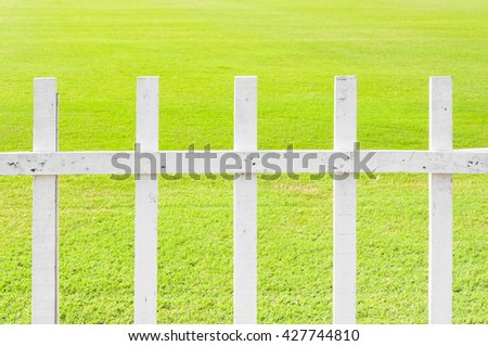 The lawn white wooden fence green grass in garden - stock photo