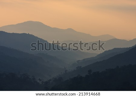 The layers of mountains at the dawn time as background