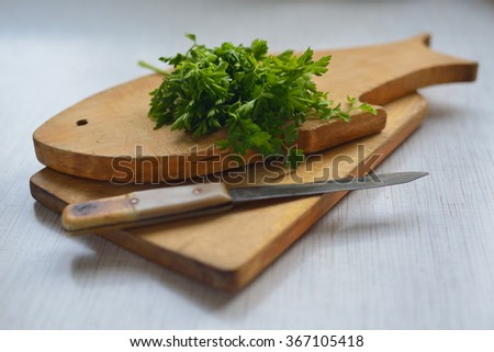 the leaves of fresh parsley and old knife on a wooden cutting Board. a small depth of field. - stock photo