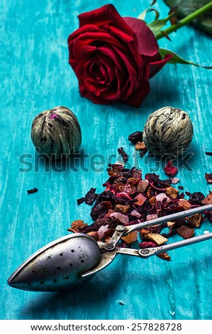 the leaves of the tea brewing on turquoise wooden background - stock photo