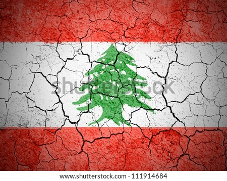 The Lebanese flag painted on cracked ground with vignette - stock photo