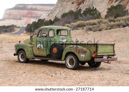The left-side rear view of an old rusty Pick-up covered with chipped green paint standing at the foot of a mountain.