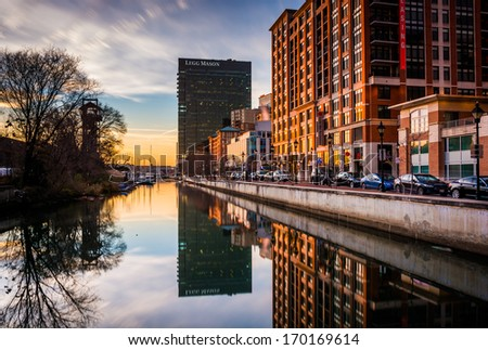 The Legg Mason Building reflecting in the water at sunset, in Harbor East, Baltimore, Maryland. - stock photo