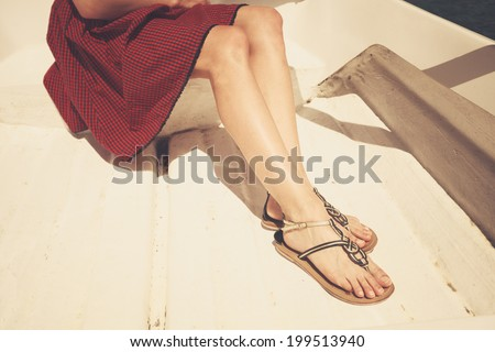 The legs and feet of a young woman sitting in a boat - stock photo