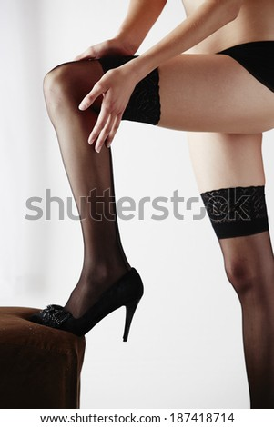 The legs of a sexy and beautiful young adult caucasian woman in black lingerie and stockings in a light white bedroom - stock photo