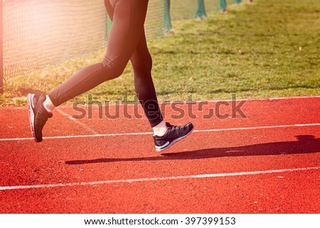 The legs of a woman running around the track on a sunny spring day. Woman running concept.  Runner jogging training workout