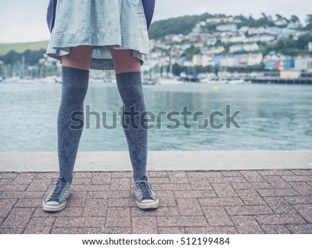 The legs of a young woman standing by a river in a small town