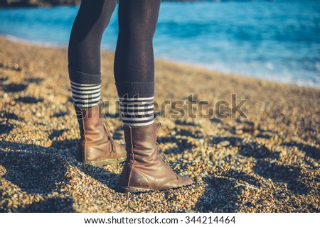 The legs of a young woman wearing stripey socks and boots as she is standing on the beach on a sunny day - stock photo