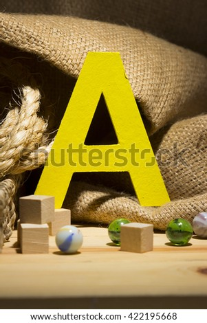 "The letter ""A "" by  Photo font "" Yellow Texture "" and subjects with active texture. Wood, burlap, glass beads. Preparation for graphic design"