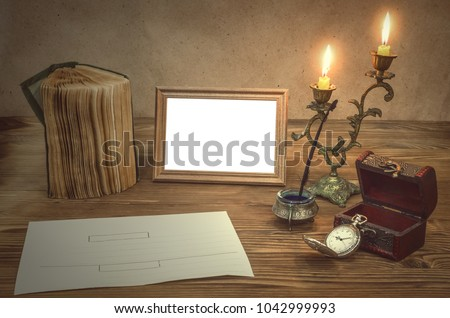 Empty Photo Frame With Copy Space, Book And Burning Candle In Vintage