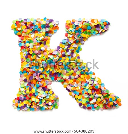 The letter K is laid out colored confetti. White background.