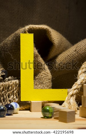 "The letter "" L "" by  Photo font "" Yellow Texture "" and subjects with active texture. Wood, burlap, glass beads. Preparation for graphic design"