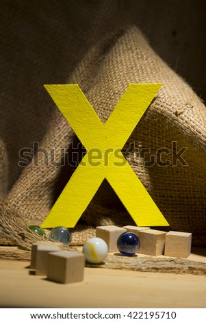 "The letter "" X "" by  Photo font "" Yellow Texture "" and subjects with active texture. Wood, burlap, glass beads. Preparation for graphic design"