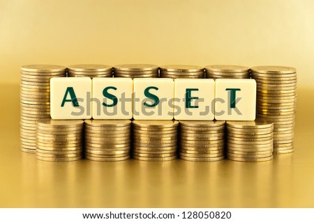 The letters  ASSET with stacks of coins on gold background