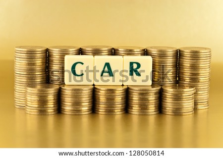 The letters  CAR with stacks of coins on gold background - stock photo