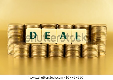 the letters DEAL with stacks of coins on gold background
