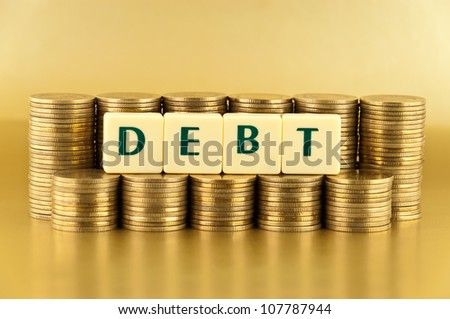 the letters DEBT with stacks of coins on gold background
