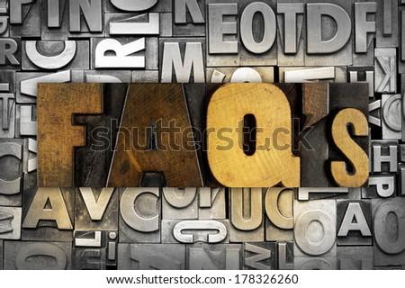 The letters FAQ's written in vintage letterpress type - stock photo