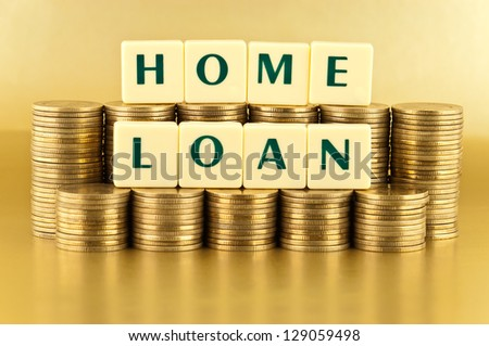 The letters HOME LOAN with stacks of coins on gold background - stock photo