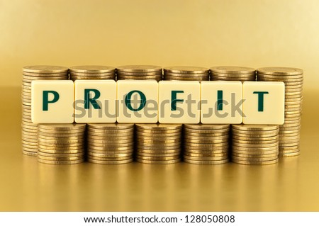 The letters PROFIT with stacks of coins on gold background - stock photo