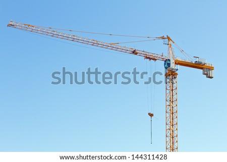 The lifting crane against blue sky - stock photo