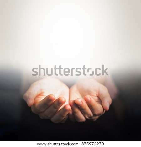 The light in hands in cupped shape. Concepts of sharing, giving, offering, taking care, protection, Friendship. - stock photo