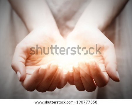 The light in young woman hands in cupped shape. Concepts of sharing, giving, offering, taking care, protection - stock photo