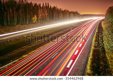The light trails of cars on a highway at night. Long exposure of fast moving traffic at a starry night. - stock photo