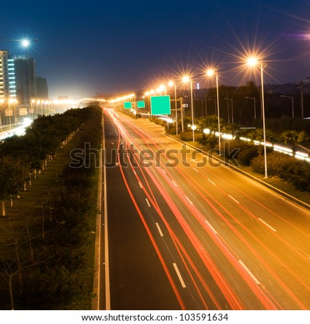 The light trails on the modern building background in urban city of China. - stock photo