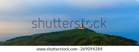 The lighthouse in Giglio Island, Tuscany Italy shot in panoramic format. This building stands on top of a hill covered by a pinewood. The landscape scene is shot at sunset.