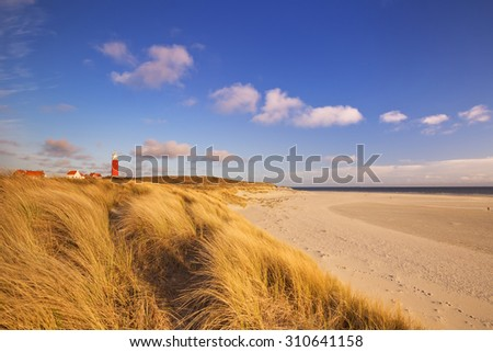 The lighthouse of the island of Texel in The Netherlands surrounded by tall sand dunes in beautiful early morning sunlight. - stock photo