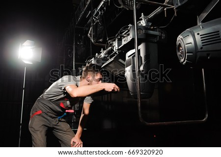The lighting engineer adjusts the lights on the stage. & Stage Worker Sets Lights Stock Photo 679053976 - Shutterstock azcodes.com