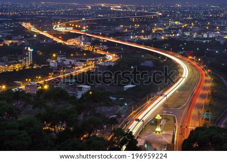 The lights of a city and road at night. - stock photo