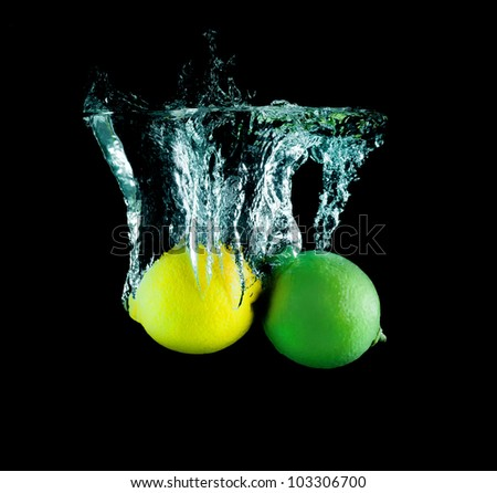 The lime and lemon on the dark background and water - stock photo