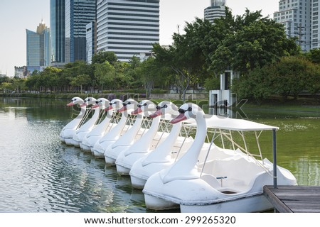 The line of Boats and Swan Pedal in the pond of the Benjakiti Park, Bangkok. - stock photo