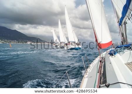 "The line of four yachts under bias. Tivat, Montenegro - 26 April, 2016. Regatta ""Russian stream"" in God-Katorskaya bay of the Adriatic Sea off the coast of Montenegro. - stock photo"