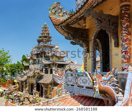 The Linh Phuoc Pagoda in mosaic style from shards of glass, pottery and porcelain in Da Lat city (Dalat) on the blue sky background in Vietnam. Da Lat is a popular tourist destination of Asia.
