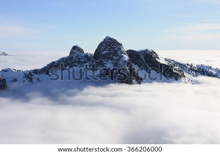 The Lions above the clouds in North Shore Mountains, BC, Canada. These mountains can be seen from many locations around Vancouver and they stand as landmarks. - stock photo