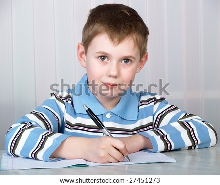 the litle boy doing homework on the table - stock photo