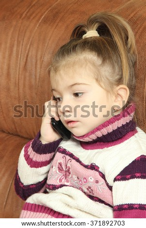 the little amusing girl communicates by the push-button mobile phone