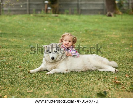 The little baby girl playing with dog against green grass